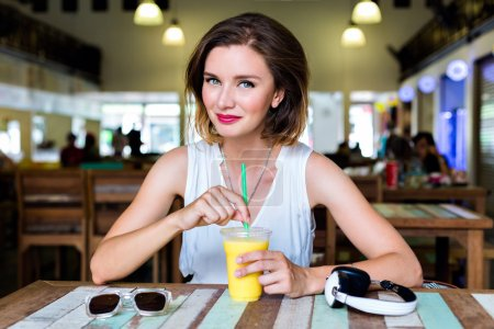 Photo for Indoor lifestyle fashion portrait of beautiful woman posing at cafe, drinking fresh healthy tasty mango juice, smiling, have nice time, bright sexy make up - Royalty Free Image