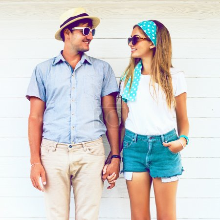 Photo for Young couple in love wearing vintage clothing hat and sunglasses, holding hands and posing at white wooden background. Vintage colours - Royalty Free Image