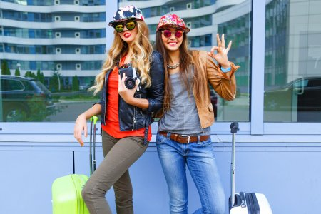 friends posing with their luggage