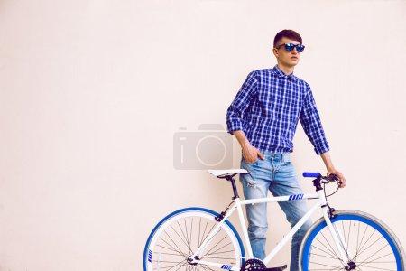 Photo pour Jeune coiffeur posant près du vélo fixe moderne et élégant, vêtu d'une chemise en pantalon bleu rétro denim et de lunettes de soleil. Fond beige, couleurs douces - image libre de droit
