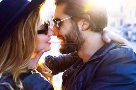 stylish sexy couple kissing on sunset