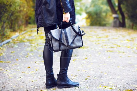 woman holding grey bag