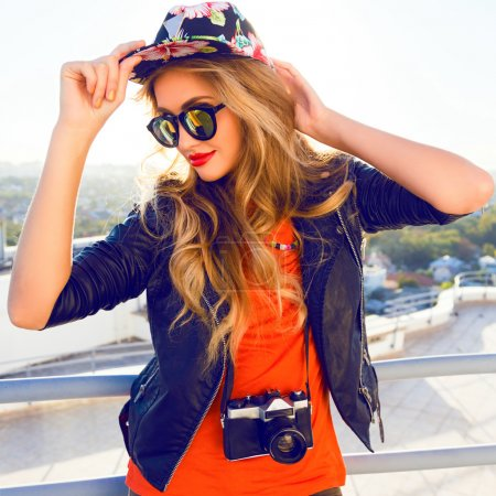 Photo pour Young sexy blonde woman posing in the roof, wearing leather jacket, swag floral hat mirrored sunglasses and bright make up, holding vintage camera, Lifestyle portrait bright toned colors - image libre de droit