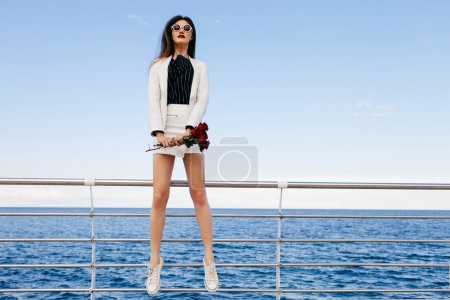 Girl jumping at embankment with bouquet of roses