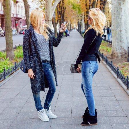 Photo pour Deux sœurs blondes faisant séance photo sur smartphone dans le parc avenue de la ville à l'automne journée ensoleillée, portant des chaussures de sport tendance et décontractées et des lunettes de soleil - image libre de droit