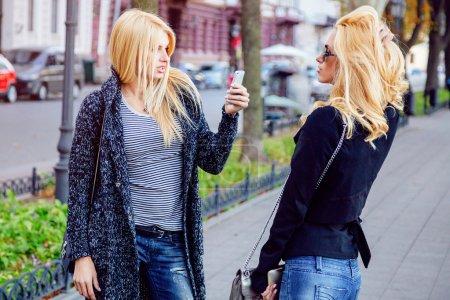 Photo pour Style de vie en plein air portrait de deux blondes élégantes meilleurs amis s'amuser et faire des photos les uns des autres sur smartphone dans belle journée d'automne - image libre de droit