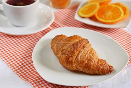 Photo for Croissant with tea and orange for breakfast - Royalty Free Image