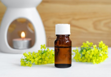 Small bottle of natural essential oil and lamp for aromatherapy