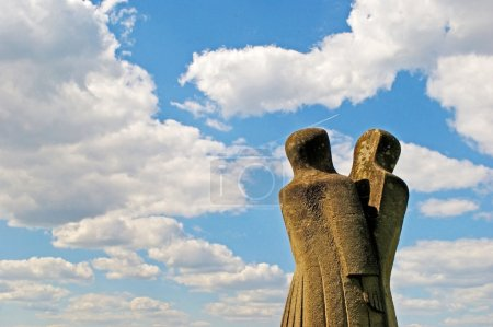 Photo pour A stone sculpture of two people (or split personality) on the background of clouds in a park in Ternopil, Ukraine - image libre de droit