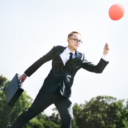 joyful businessman with balloon
