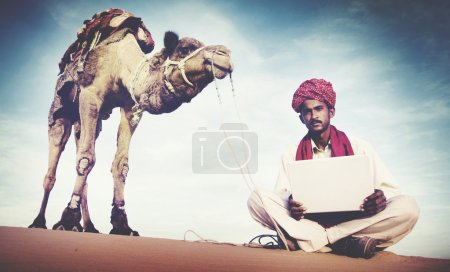 Man Using Laptop in Desert