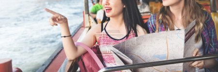 Photo for Girls Traveling with Map sightseeing in boat - Royalty Free Image
