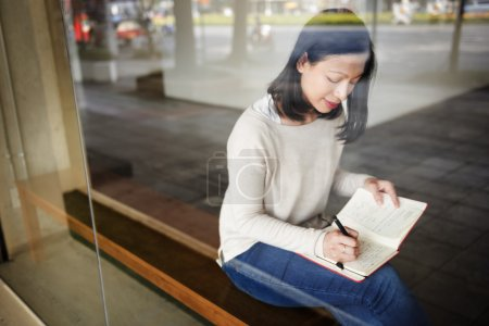 Asian Lady Writing in Notebook