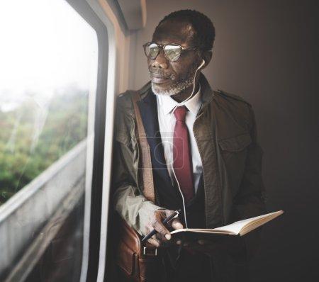 man writing in notebook in train