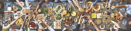 Foto de Amigos de diversidad comer para mesa grande con diferentes alimentos y bebidas, vista superior - Imagen libre de derechos