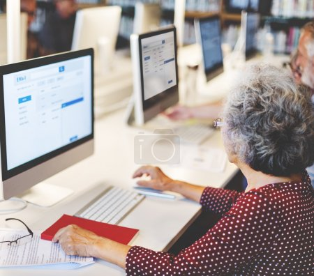 Senior woman and man using computers