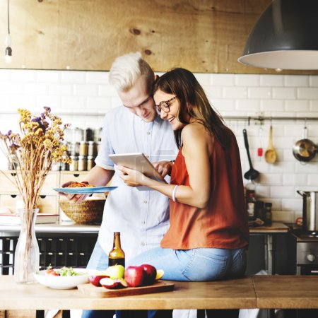 couple in kitchen with  digital device