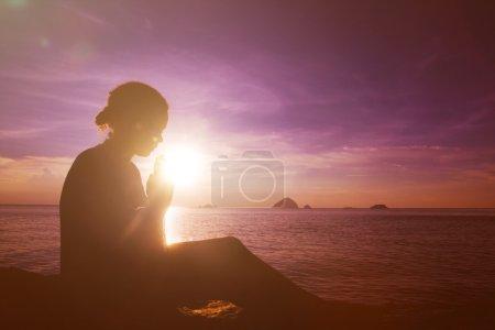 Young woman praying at sunsets
