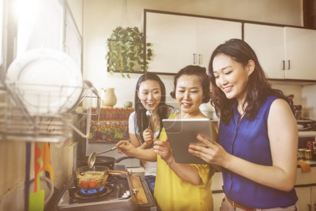 asian mother with daughters cooking in kitchen