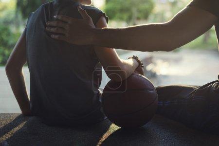 Sportsman teaching boy play Basketball