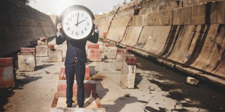 businessman holding big clock