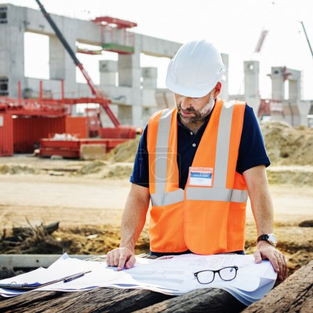 construction Worker examines drawings