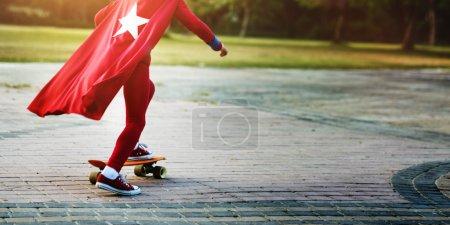 Superhero Kid riding on Skateboard