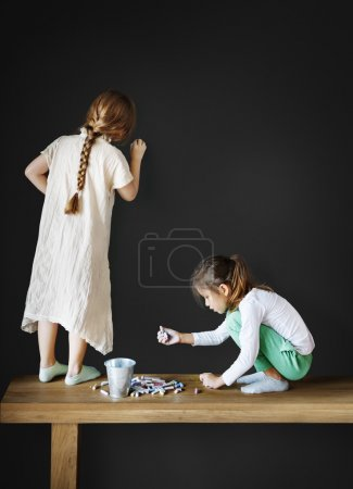 Girls drawing on Blackboard