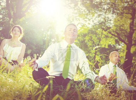 business people meditating outdoors
