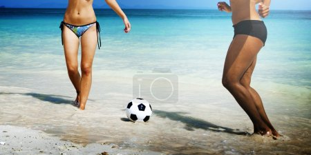 Photo for Young friends enjoying at tropical beach, playing football - Royalty Free Image