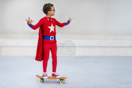 Superhero Kid riding on Skateboard