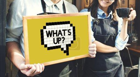 baristas near cafe holding blackboard