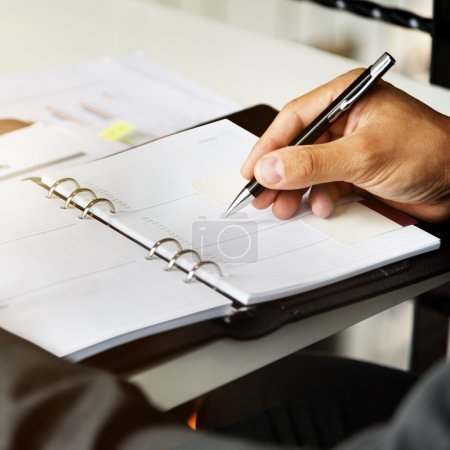 Businessman writing notes in diary