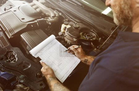man mechanic writing notes about car