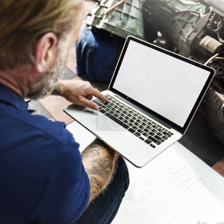 car mechanic with laptop in Garage