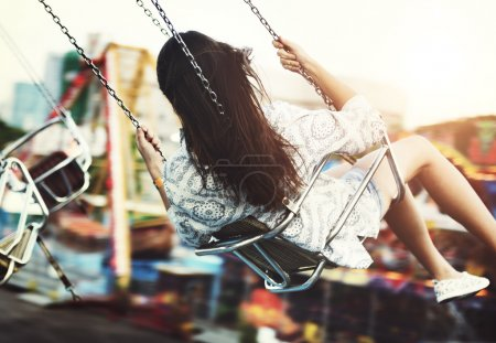 Girl riding on swing in Amusement Park