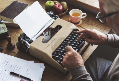 senior man writing on typewriter machine