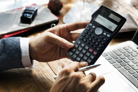 businessman counting on calculator