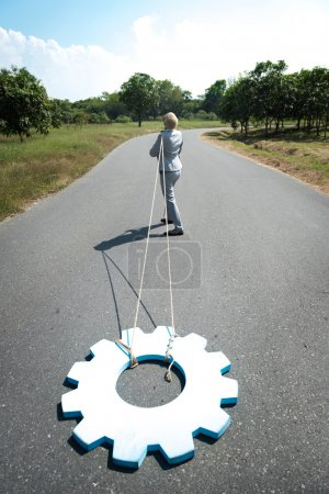 businesswoman pulls gear wheel