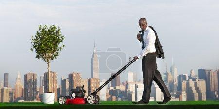 Green Businessman mowing lawn