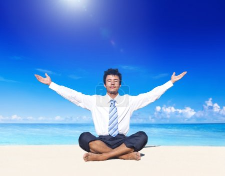 Businessman meditating on beach