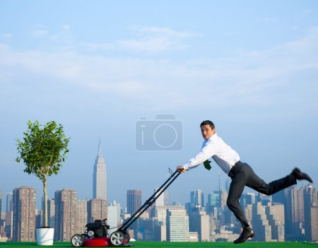 Green businessman mowing lawn