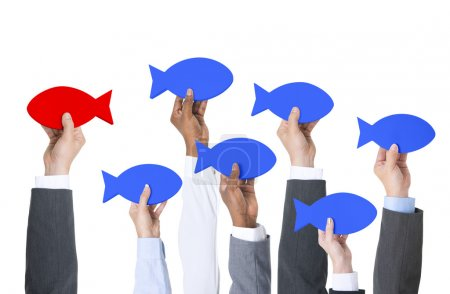 Business people holding paper fish