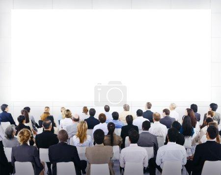 Photo pour Groupe de gens d'affaires assis et regardant la présentation vierge - image libre de droit