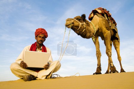 Indian man with laptop and camel