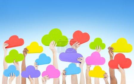 Hands holding cloud shaped speech bubbles