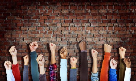 Hands Raised on Brick Wall