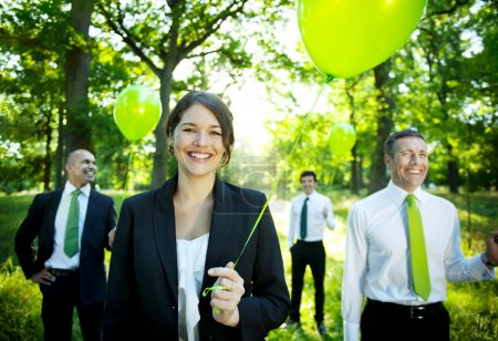 Business people holding green balloons