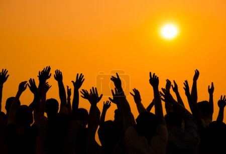 People raised hands up on sunset