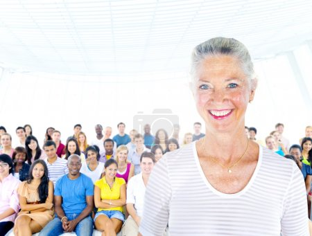 Senior woman standing out from crowd